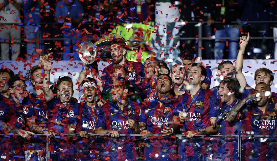 Barcelona players celebrate with the trophy after the Champions League final soccer match between Juventus Turin and FC Barcelona at the Olympic stadium in Berlin Saturday, June 6, 2015. Barcelona won the match 3-1.  (AP Photo/Frank Augstein)