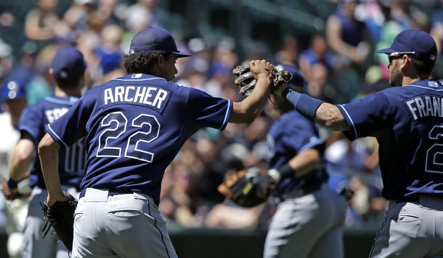 Tampa Bay Rays starting pitcher Chris Archer (22) reaches to share congratulations with shortstop Nick Franklin after infielders successfully completed a rundown of Seattle Mariners' Nelson Cruz on a stolen base attempt in the fourth inning of a baseball game, Sunday, June 7, 2015, in Seattle. (AP Photo/Elaine Thompson)