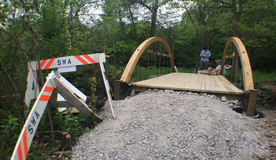 Construction signs from Selzer Werderitsch Associates stand before the nearly finished bridge on May 16, 2015 at Hickory Hill Park in Iowa City, Iowa. The bridge was constructed by volunteers and local Boy Scouts. (Zach Berg/Iowa City Press-Citizen via AP)  NO SALES