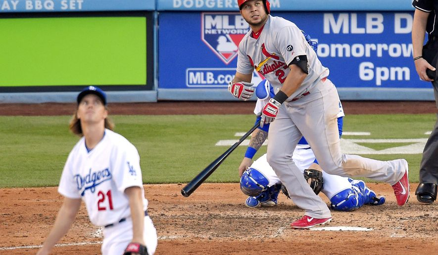 St. Louis Cardinals' Jhonny Peralta, right, hits a solo home run as Los Angeles Dodgers starting pitcher Zack Greinke, left, watches during the sixth inning of a baseball game, Sunday, June 7, 2015, in Los Angeles. (AP Photo/Mark J. Terrill)