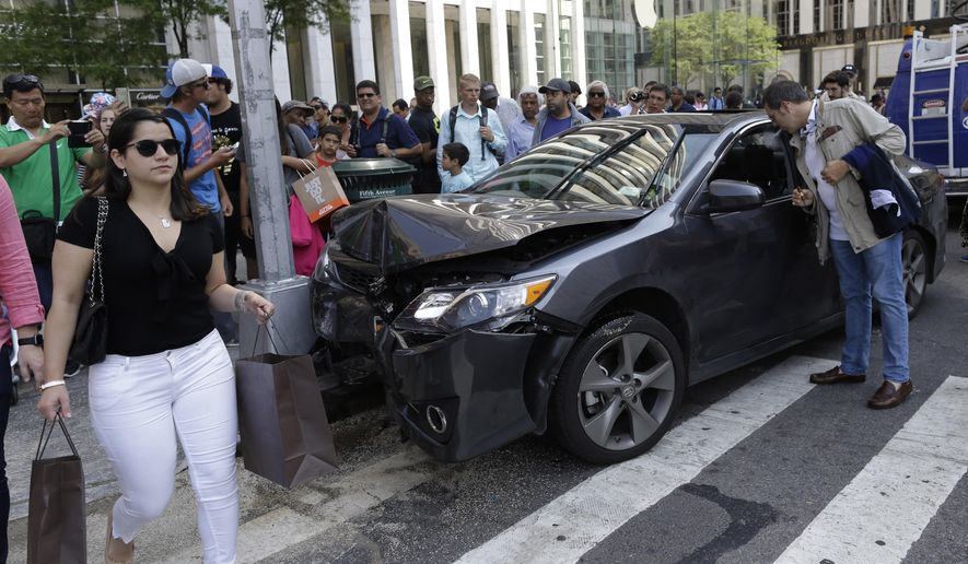 Pedestrians walk past a vehicle involved in an crash on the corner of 59th Street and Fifth Avenue, Monday, June 8, 2015, in New York. The Fire Department of New York says a vehicle struck pedestrians near Central Park and The Plaza Hotel, injuring four people, some with serious injuries. (AP Photo/Mary Altaffer)