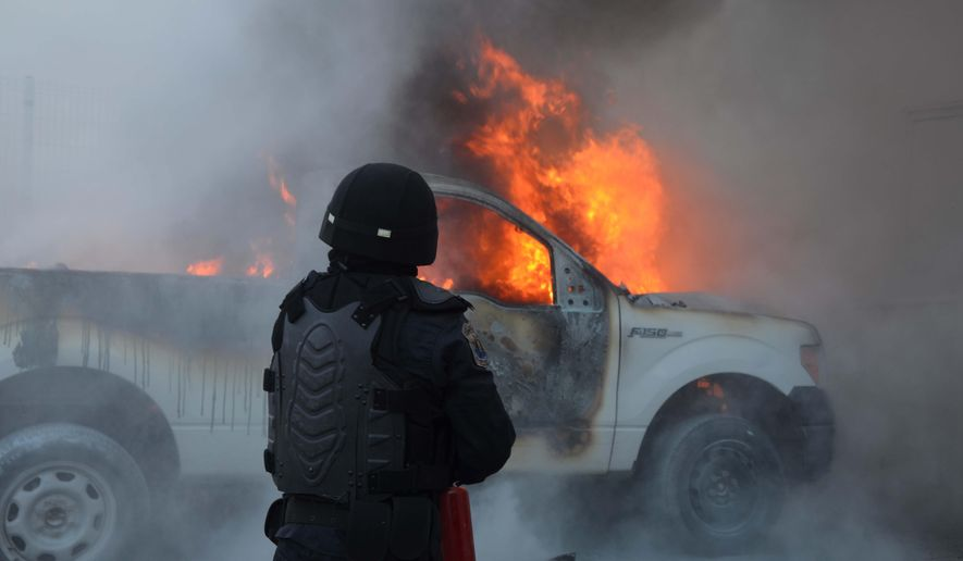 A riot policeman use extinguishers to put out the flames of a burning pick-up truck after it was set on fire in the state capital of Chilpancingo, Guerrero state, Sunday, June 7, 2015. Next to the truck several molotov bombs were found. The incident comes on the day of the mid-term elections as a loose coalition of radical teachers' unions and activists vowed to block the vote for 500 seats in the lower house of Congress, nine of 31 governorships and hundreds of mayors and local officials. (AP Photo/Alejandrino Gonzalez)