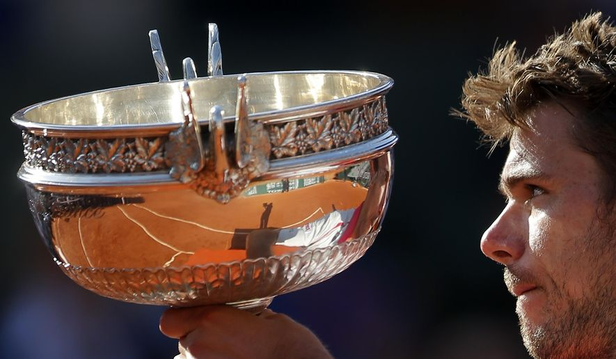 Switzerland's Stan Wawrinka holds the cup after defeating Serbia's Novak Djokovic in  their final match of the French Open tennis tournament at the Roland Garros stadium, Sunday, June 7, 2015 in Paris. Wawrinka won 4-6, 6-4, 6-3, 6-4. (AP Photo/Francois Mori)