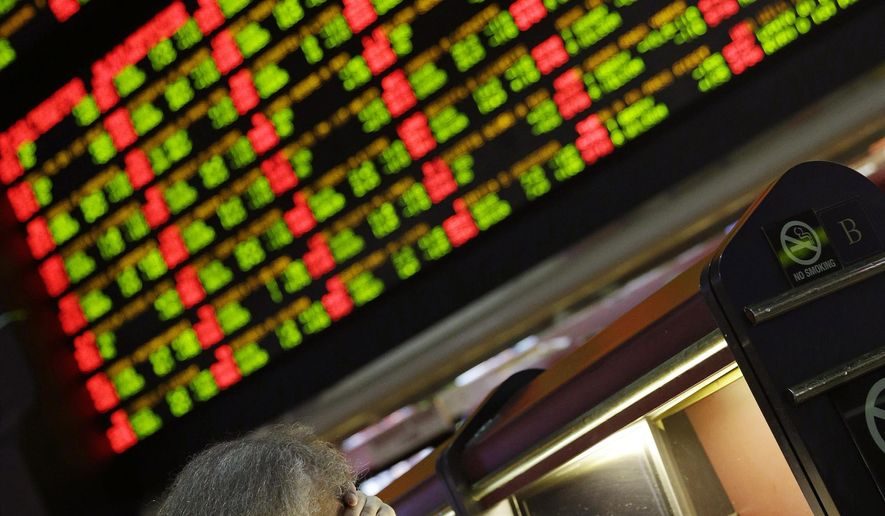 FILE- In this Jan. 27, 2015 file photo, a man looks through Super Bowl proposition bets at the Westgate Superbook Race and Sportsbook in Las Vegas. A board behind displays the odds for different proposition bets.  A new Nevada law allows investors looking for a stock market alternative to wager their money in the state on sports instead. (AP Photo/John Locher, File)