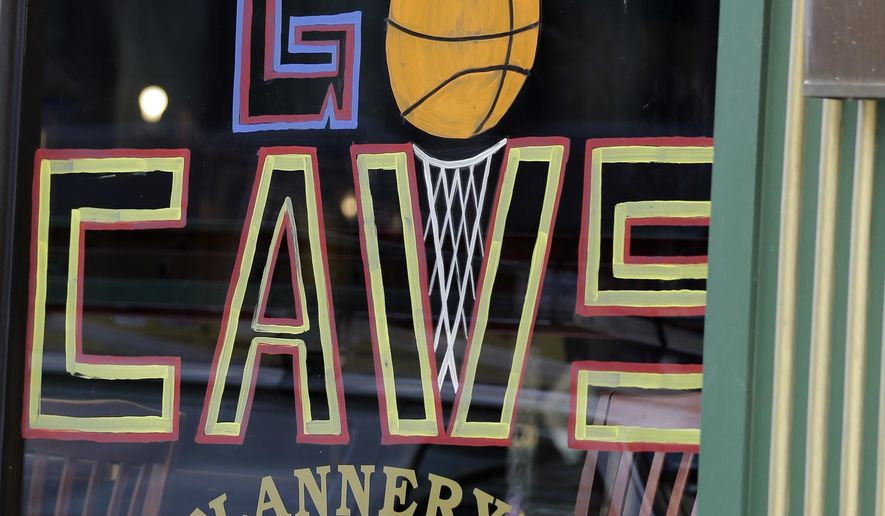 """In this photo taken, Friday, June 5, 2015, a woman walks past """"Let's Go Cavs"""" signage on a pub in Cleveland. Behold a new, shining Cleveland, once dubbed the Mistake on the Lake. Well, times have changed, and so have the attitudes of skeptical and cynical Cleveland fans, many of whom grew up hoping for the best, expecting the worst and agonizing through moments that have earned dubious nicknames: Red Right 88, The Drive, The Fumble, The Shot, The Move, The Decision. One man has transformed this town. LeBron James has Cleveland believing. (AP Photo/Tony Dejak)"""