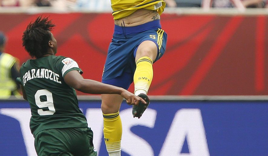Sweden's Nilla Fischer (5) heads the ball past Nigeria's Desire Oparanozie (9) during the first half of a FIFA Women's World Cup soccer match in Winnipeg, Manitoba, Monday, June 8, 2015. (John Woods/The Canadian Press via AP) MANDATORY CREDIT