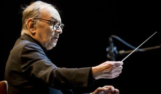 FILE -- In this Feb. 15, 2014 file photo Italian composer Ennio Morricone conducts the Modern Art Orchestra of Hungary during a concert of his film scores in Papp Laszlo Budapest Sports Arena in Budapest. Oscar-winning Italian composer Ennio Morricone this week will premiere a Mass he composed to mark the 200th anniversary of the restoration of the Jesuit order and named for its most illustrious member, Pope Francis. (AP Photo/MTI, Balazs Mohai, File)