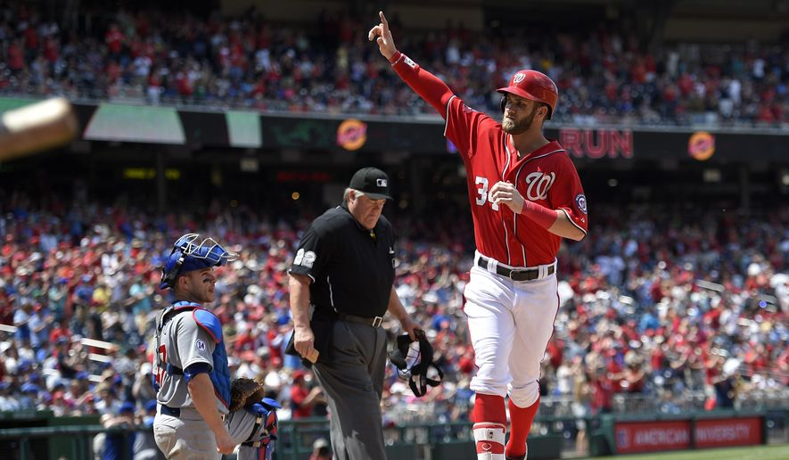 Washington Nationals' Bryce Harper (34) celebrates his home run as Chicago Cubs catcher Miguel Montero, looks on at left, during the ninth inning of a baseball game, Saturday, June 6, 2015, in Washington. The Cubs won 4-2. Also seen is home plate umpire Joe West at center. (AP Photo/Nick Wass)