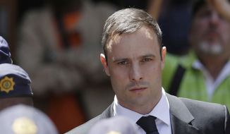 In this Friday, Oct. 17, 2014, file photo, Oscar Pistorius is escorted by police officers as he leaves the high court in Pretoria, South Africa. (AP Photo/Themba Hadebe, File)