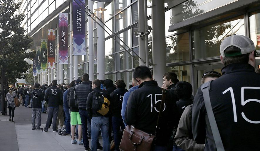 Attendees line up outside of the Moscone West building for the first day of the Apple Worldwide Developers Conference in San Francisco, Monday, June 8, 2015. The maker of iPods and iPhones is expected to announce its new, paid streaming-music service to launch this summer. (AP Photo/Jeff Chiu)