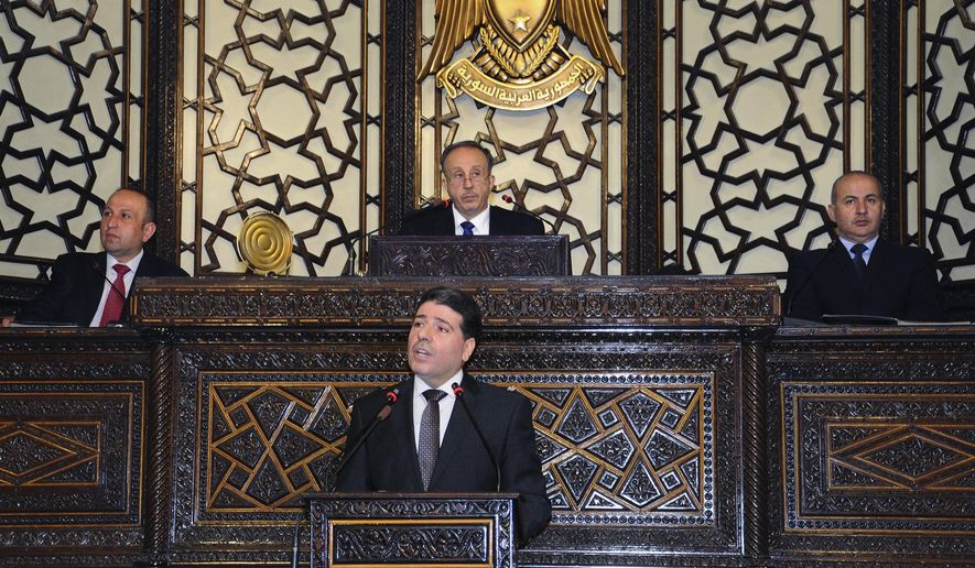 In this photo released by the Syrian official news agency SANA, Syrian Prime Minister Wael al-Halqi, center front, speaks during a parliament session in Damascus, Syria, Monday, June 8, 2015. Al-Halqi called on young Syrians Monday to fulfill their mandatory military service obligation, promising better pay for troops on the front lines as well as one meal of hot food a day. (SANA via AP)