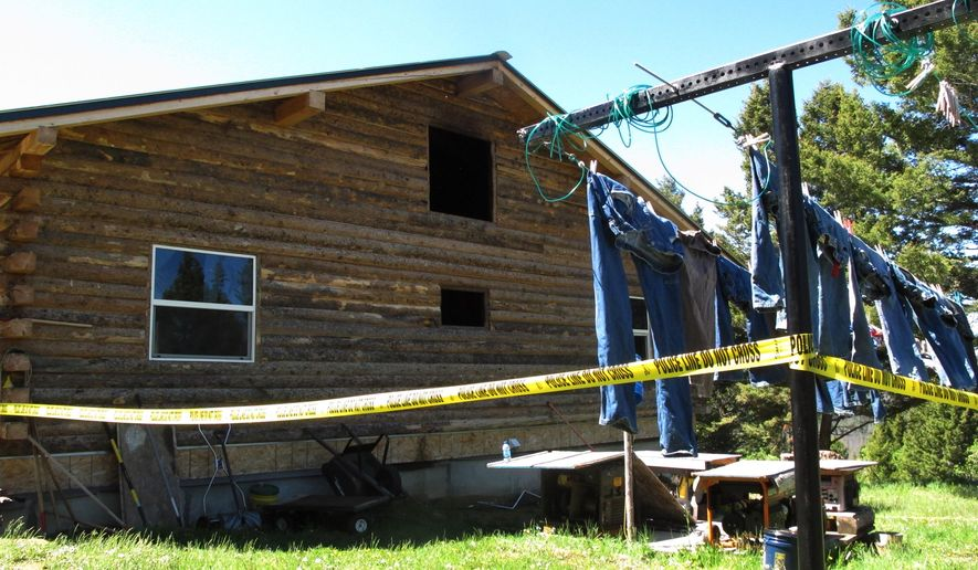 Police tape rings a fire-damaged cabin in the Beaverhead-Deer Lodge Forest outside Deer Lodge, Mont., on Monday, June 8, 2015, where a Montana man shot and killed his wife and three children, set a fire in the family's remote cabin and then killed himself, officials in Anaconda-Deer Lodge County said. The shootings happened Sunday morning at a one-room log cabin in the Beaverhead-Deerlodge National Forest about 15 miles southeast of the town of Deer Lodge, Police Chief Tim Barkell said. Barkell was withholding the names of the victims and the shooter until relatives could be notified. (AP Photo/Matt Volz)