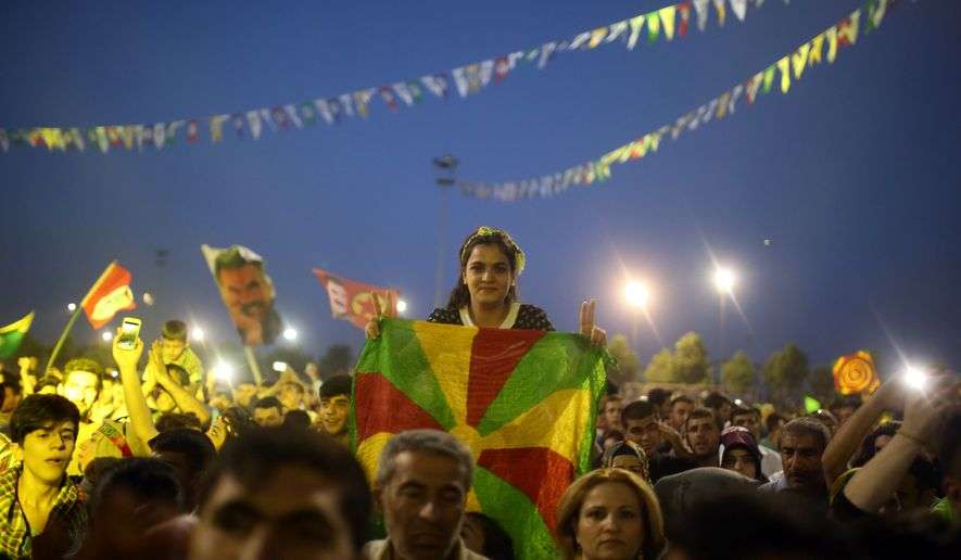 Supporters of pro-Kurdish Peoples's Democracy Party celebrate election results in Diyarbakir, Turkey, Monday. Turkey's long-ruling Justice and Development Party of President Recep Tayyip Erdogan has suffered strong losses in parliamentary elections that will force it to seek a coalition partner for the next government, but other parties vowed to resist any pact. (Associated Press)
