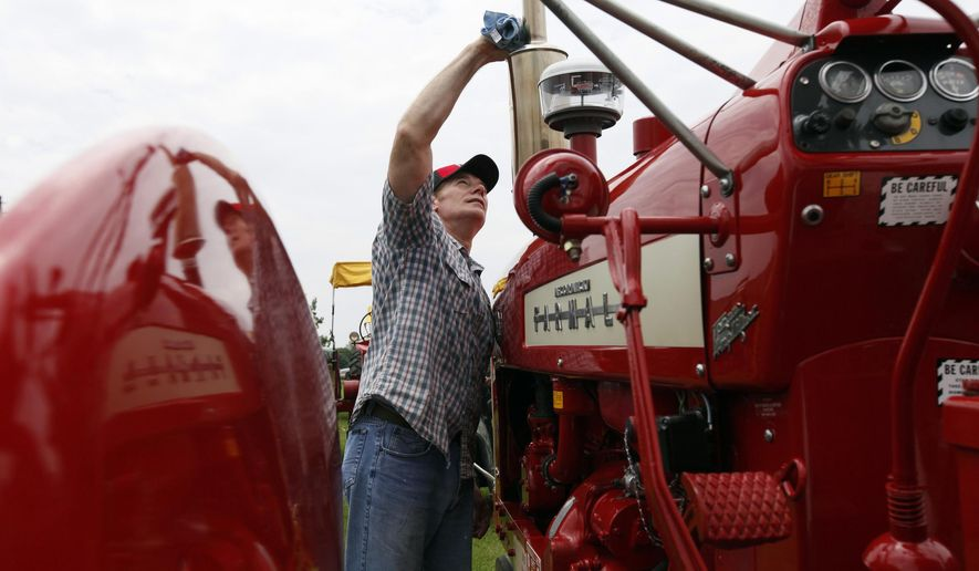 In this Sunday, June 7, 2015 photo, Iowa native Ted Lockwood, of Norton, Va., polishes his Farmall 450 at the 16th Annual Great Eastern Iowa Tractorcade at Midwest Old Thresher Grounds in Mount Pleasant, Iowa. Nearly 500 vehicles are expected to join the Great Eastern Iowa Tractorcade this year. (Lauren Kastner/The Hawk Eye via AP)