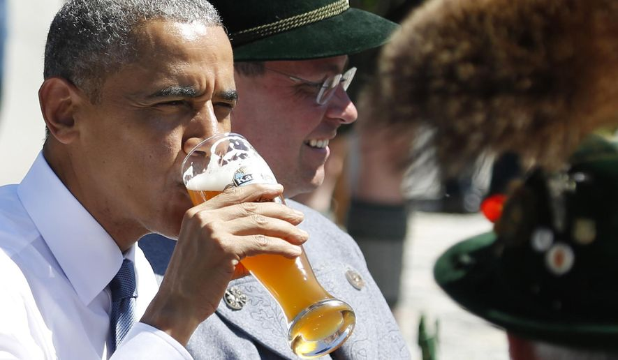 President Obama drinks a beer as he sits between men dressed in traditional Bavarian clothes during a visit to the village of Kruen in southern Germany on June 7, 2015, prior to the G-7 summit. (Associated Press)