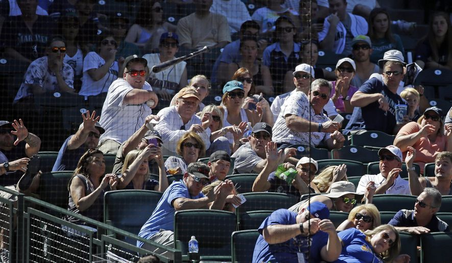 Fans duck as a bat from Seattle Mariners' Rickie Weeks flies into the stands behind home plate in the eighth inning of a baseball game against the Tampa Bay Rays Sunday, June 7, 2015, in Seattle. No one was injured. (AP Photo/Elaine Thompson)