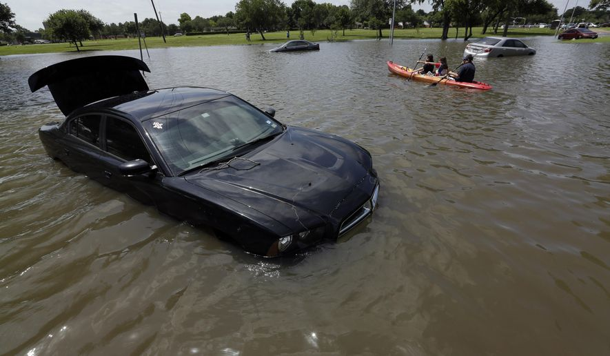 FILE - In this May 26, 2015 file photo a  boat is paddled down a flooded street in Houston. Feeling soggy? Federal officials calculate that last month was the wettest on record for the contiguous U.S. On average 4.36 inches of rain and snow fell over the Lower 48 in May, sloshing past October 2009 which had been the wettest month in U.S. records with 4.29 inches. Records go back to 1895. National Oceanic and Atmospheric Administration (NOAA)  climate scientist Jake Crouch calculated that comes to more than 200 trillion gallons of water in May. (AP Photo/David J. Phillip, File)