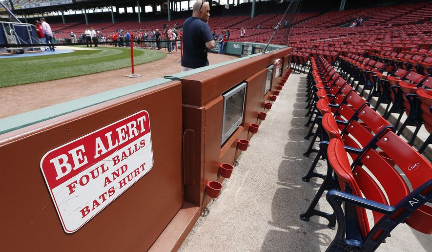 A warning sign is displayed in the stands at Fenway Park before a baseball game between the Boston Red Sox and the Oakland Athletics in Boston, Saturday, June 6, 2015. A woman was hit and seriously injured by a broken bat during the game on Friday. (AP Photo/Michael Dwyer)
