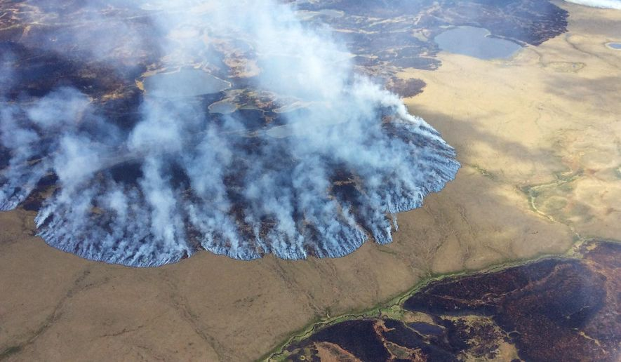 In this Sunday, June 7, 2015 photo, smoke rises from the Bogus Creek Fire, one of two fires burning in the Yukon Delta National Wildlife Refuge in southwest Alaska. Fire managers said Monday that weekend rain helped tamp down the fires which, together, total about 63 square miles. (Matt Snyer/Alaska Division of Forestry via AP)