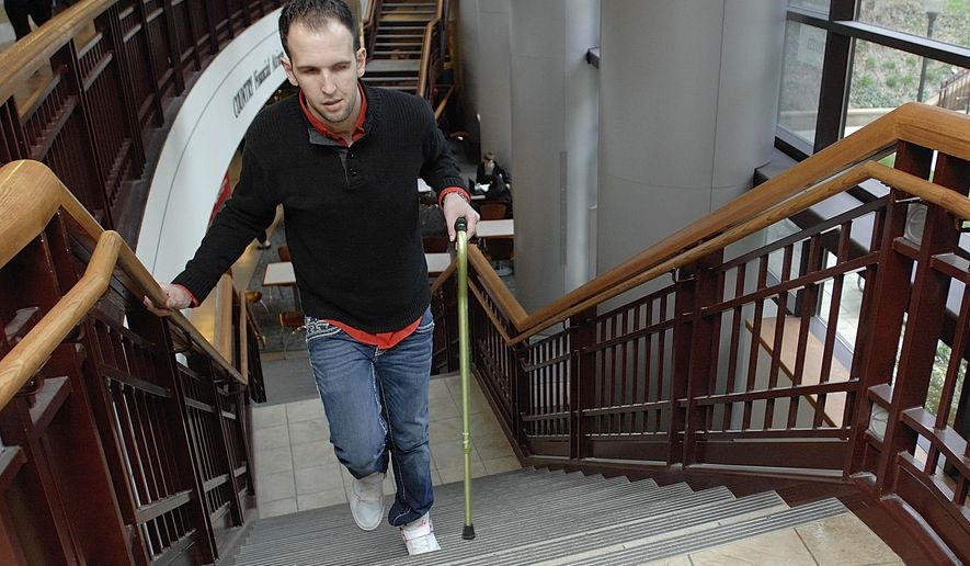 In this March 29, 2015 photo, Mike Trujillo, of Bollingbrook, Ill., walks up the steps at State Farm Hall at Illinois State University in Normal, Ill. He will graduate in 2015 with a degree in business from Illinois State University at the age of 25. A stroke seven years ago delayed his attending college, but he hopes his story will encourage others. (Lori Ann Cook-Neisler, The Pantagraph via AP)