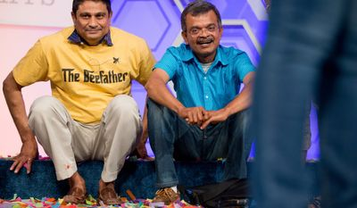 Mirle, left, the father of Vanya Shivashankar, 13, of Olathe, Kan., and Krishnan, the father of Gokul Venkatachalam, 14, of St. Louis, sit onstage together after their children are named co-champions of the Scripps National Spelling Bee, Thursday, May 28, 2015, in Oxon Hill, Md. (AP Photo/Andrew Harnik)