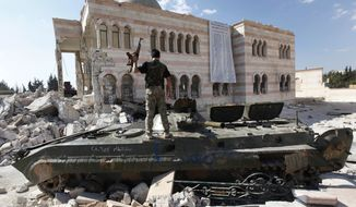 A Free Syrian Army soldier stands on a damaged Syrian military tank in front of a damaged mosque, which were destroyed during fighting with government forces, in the Syrian town of Azaz, on the outskirts of Aleppo on Sept. 23, 2012. Syrian rebels on May 8, 2015, voiced serious reservations about a U.S. program to train moderate rebels which U.S. and Jordanian officials say has kicked off in Jordan, dismissing it as a drop in the ocean that would not change realities on the ground. (Associated Press) **FILE**