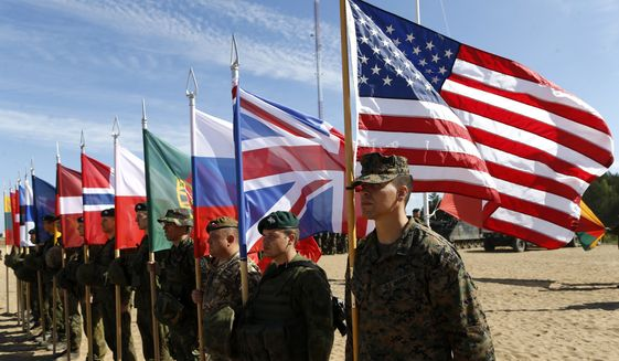 Soldiers from NATO countries attend a opening ceremony of military exercise 'Saber Strike 2015', at the Gaiziunu Training Range in Pabrade some 60km.(38 miles) north of the capital Vilnius, Lithuania, Monday, June 8, 2015. The annual multinational Exercise Saber Strike 2015 organized by the U. S. Army in Europe (USAREUR) on June 1 through 19 comprises brigade-level command post exercises held concurrently in all the three Baltic States and Poland. This year the exercise will train the record number of 6,000 troops from 13 NATO member and partner states - Denmark, Estonia, U.S.A., UK, Canada, Latvia, Poland, Lithuania, Norway, Germany, Portugal, Slovenia and Finland. (AP Photo/Mindaugas Kulbis)