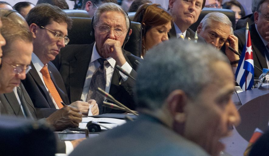 Cuban President Raul Castro (center) listens as President Obama delivers his speech to world leaders at the VII Summit of the Americas' opening plenary April 11 in Panama City, Panama. (Associated Press)
