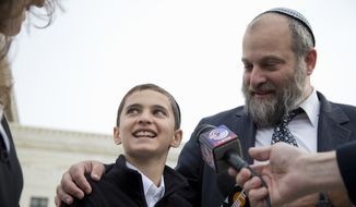 In this Nov. 3, 2014, file photo, Menachem Zivotofsky and his father Ari Zivotofsky speaks to media outside the Supreme Court in Washington. The Supreme Court has struck down a disputed law that would have allowed Americans born in Jerusalem to list their birthplace as Israel on their U.S. passports. It's an important ruling that underscores the president's authority in foreign affairs. (AP Photo/Carolyn Kaster, File)