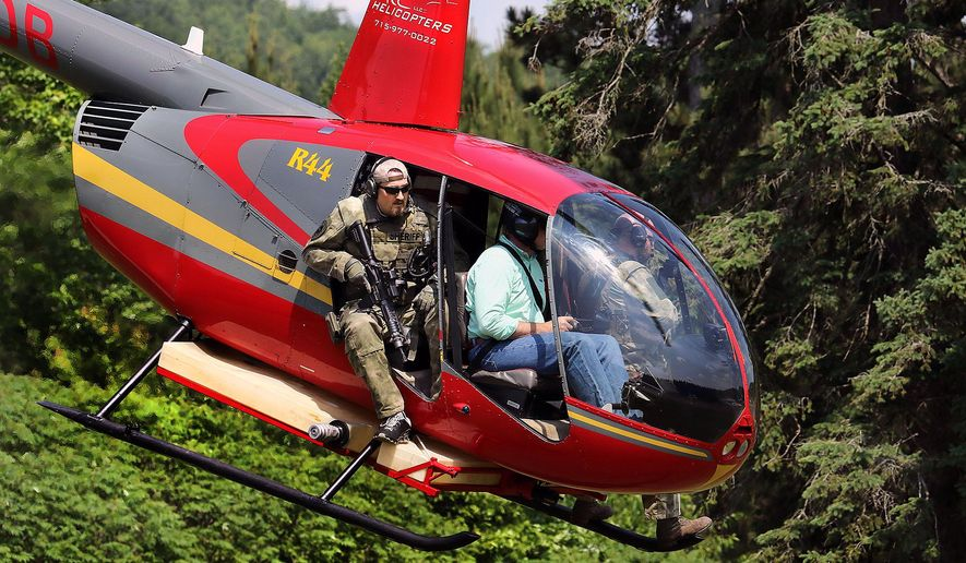 Sheriff's deputies ride in a helicopter as they search rural Eau Claire County (Wis.)  Monday, June 8, 2015 for an armed man who abducted a woman in suburban Milwaukee.  The woman eventually escaped at an Eau Claire convenience store and the perpetrator then led police on a high-speed chase before abandoning his vehicle and fleeing into a wooded area. (Steve Kinderman/Eau Claire Leader-Telegram via AP)