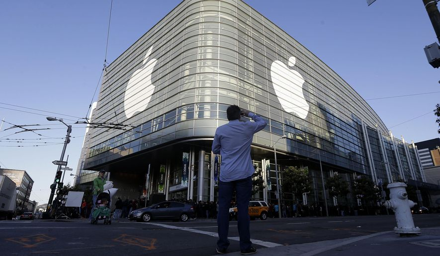 Apple logos adorn the exterior of the Moscone West building on the first day of the Apple Worldwide Developers Conference in San Francisco, Monday, June 8, 2015. The maker of iPods and iPhones is expected to announce its new, paid streaming-music service to launch this summer. (AP Photo/Jeff Chiu)