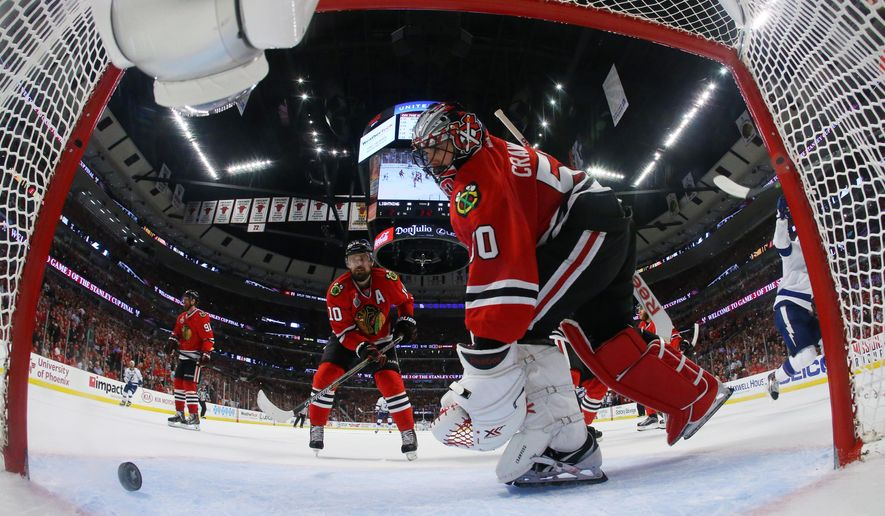 Chicago Blackhawks goalie Corey Crawford (50) and left wing Patrick Sharp (10) look at the puck after Tampa Bay Lightning center Cedric Paquette (13) scores a goal during the third period in Game 3 of the NHL hockey Stanley Cup Final on Monday, June 8, 2015, in Chicago. The Lightning won 3-2 to take a 2-1 lead in the series. (Bruce Bennett/Pool Photo via AP)
