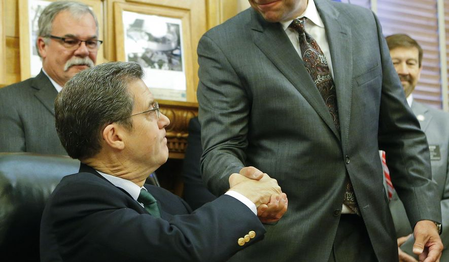 Kansas Secretary of State Kris Kobach, right, shakes hands with Gov. Sam Brownback on Monday, June 8, 2015, at the Kansas Statehouse in Topeka, Kan., after the signing of Senate Bill 34, a bill that grants persecuting power to the Secretary of State for cases of voter fraud.  (Chris Neal/The Topeka Capital-Journal via AP)