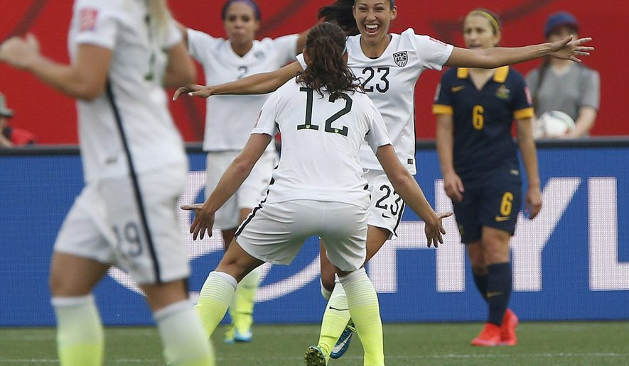 United States' Christen Press (23) celebrates her goal against Australia with Lauren Holiday (12) during a FIFA Women's World Cup soccer match in Winnipeg, Manitoba, Monday, June 8, 2015. (John Woods/The Canadian Press via AP) MANDATORY CREDIT