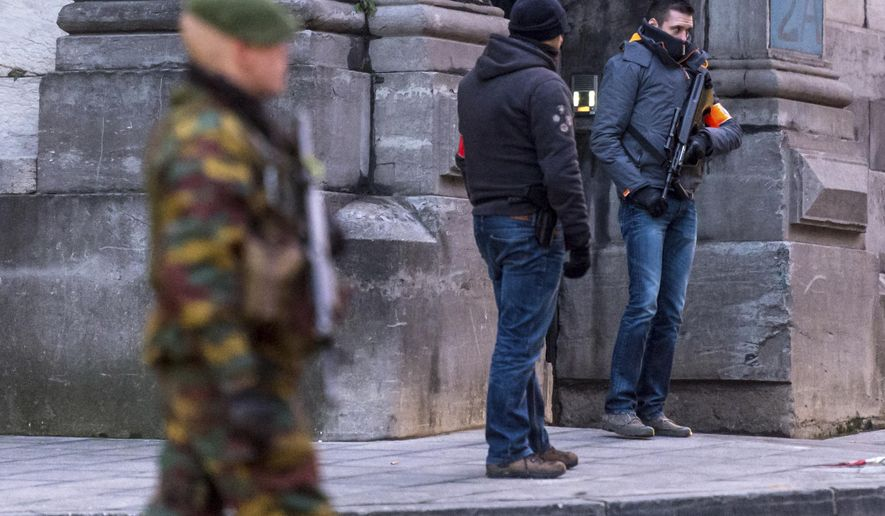 FILE - In this Wednesday, Jan. 21, 2015 file photo, a Belgian para-commando and anti-terror squad policemen guard the parking area at the Palace of Justice, where suspects wanted in Belgium on terrorism-related charges have to appear before the federal court in Brussels. On Monday June 8, 2015 Belgian police arrested 16 people  in twin terrorism-related investigations involving Chechen extremists, authorities said. Members of one group, based in western Flanders, were allegedly active in Syria and probably participated in combat there, prosecutors said. (AP Photo/Geert Vanden Wijngaert, File)