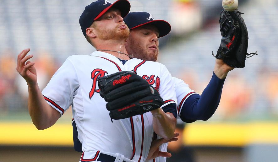 Atlanta Braves first baseman Freddie Freeman, right, who called the ball, is unable to hold on to a foul ball by San Diego Padres' Justin Upton as pitcher Shelby Miller collides with him during the first inning of a baseball game Monday, June 8, 2015, in Atlanta. (Curtis Compton/The Canadian Press via AP) MANDATORY CREDIT