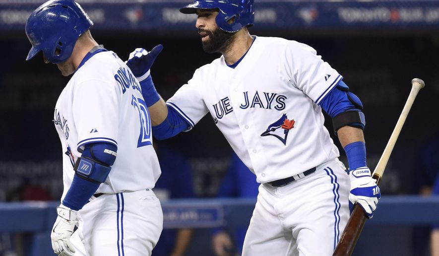 Toronto Blue Jays' Jose Bautista congratulates Josh Donaldson after his solo home run in the second inning of a baseball game against the Miami Marlins, Monday, June 8, 2015, in Toronto. (Frank Gunn/The Canadian Press via AP) MANDATORY CREDIT