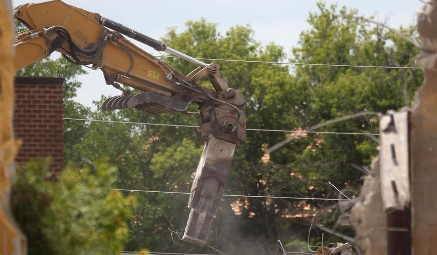 In a Thursday, June 5, 2015 photo, demolition continues at the former wastewater treatment plant on South Clinton Street in Iowa City, Iowa, to make way for a new city park. The plant was decommissioned last year because of its vulnerability to flooding. (David Scrivner/Iowa City Press-Citizen via AP)  NO SALES
