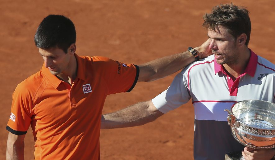 French Open winner Stan Wawrinka, right, looks at Serbia's Novak Djokovic as he leaves the podium after the men's final of the French Open tennis tournament at the Roland Garros stadium, in Paris, France, Sunday, June 7, 2015. Wawrinka won in in four sets, 4-6, 6-4, 6-3, 6-4. (AP Photo/David Vincent)