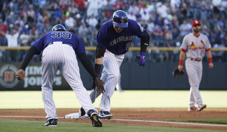 Colorado Rockies' Troy Tulowitzki, front right, is congratulated by third base coach Stu Cole, front left, as Tulowitzki circles the bases after hitting a three-run home run off St. Louis Cardinals starting pitcher John Lackey in the first inning of a baseball game Monday, June 8, 2015, in Denver. (AP Photo/David Zalubowski)