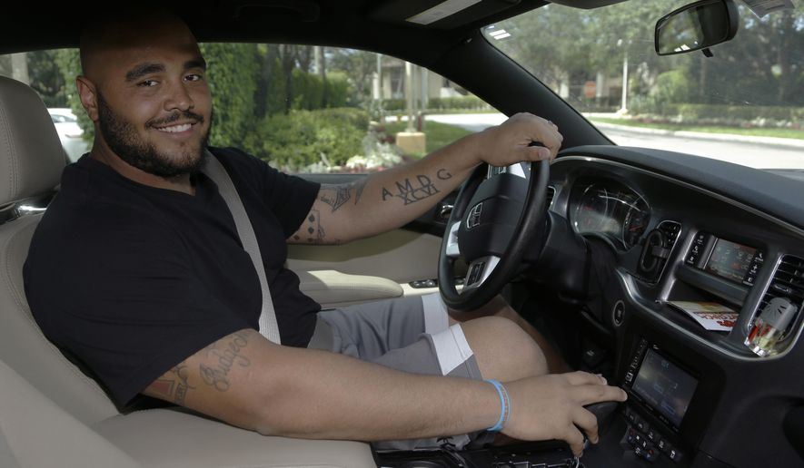 Miami Dolphins defensive lineman A.J. Francis poses inside his vehicle after an NFL football organized team activity, Monday, June 8, 2015, in Davie, Fla. Francis wants to help the Dolphins make the playoffs, but this offseason he has other destinations in mind-he's working as an Uber driver. (AP Photo/Lynne Sladky)