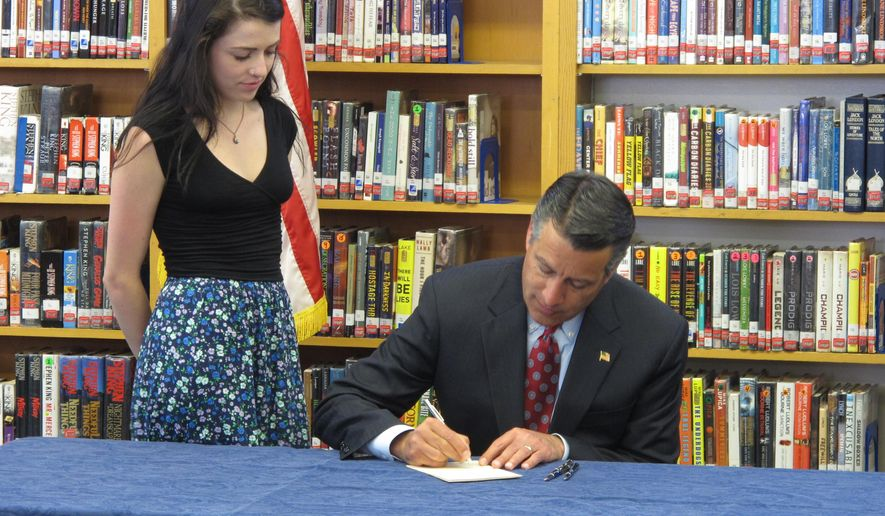 Nevada Gov. Brian Sandoval signs into law on Monday, June 8, 2015, a measure creating millions of dollars in incentives to combat the state's teacher shortage as his daughter, Maddy, watches in the library at Reno High School where she is a senior. (AP Photo/Scott Sonner)