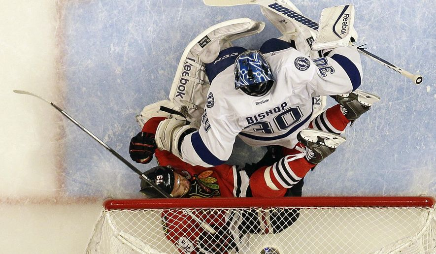 Chicago Blackhawks' Jonathan Toews, bottom, falls into the net past Tampa Bay Lightning goalie Ben Bishop during the first period in Game 3 of the NHL hockey Stanley Cup Final on Monday, June 8, 2015, in Chicago. (AP Photo/Nam Y. Huh)