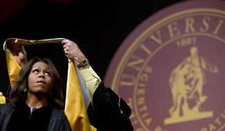 FILE - In this May 9, 2015, file photo, first lady Michelle Obama is presented with a robe and honorary degree at the Tuskegee University's spring commencement in Tuskegee, Ala. Graduation season is winding down but among the eight commencement addresses given this year by three of the biggest names, President Barack Obama, first lady Michelle Obama and Vice President Joe Biden, a few moments stood out that may last a little longer. (AP Photo/Brynn Anderson)