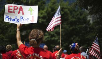 Claire Harrison, of Alpharetta, Ga., protests the Environmental Protection Agency during a July 29, 2014, rally in Atlanta in response to an EPA hearing on tougher pollution restrictions. (Associated Press) **FILE**