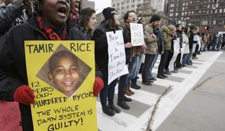 FILE- In this Nov. 25, 2014, file photo, demonstrators block Public Square Tuesday, Nov. 25, 2014, in Cleveland, during a protest over the police shooting of 12-year-old Tamir Rice. A group of civil rights leaders, activists and clergy plans to seek arrest warrants for two police officers involved in the shooting death Rice. The group plans to make court filings Tuesday, June 9, 2015, under an Ohio law allowing private citizens with knowledge of a case to file affidavits charging an offense and asking a judge to issue arrest warrants.  (AP Photo/Tony Dejak, File)