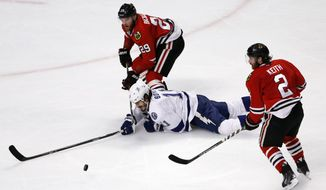 Tampa Bay Lightning's Brian Boyle, center, tries to reach a loose puck as he falls between Chicago Blackhawks' Bryan Bickell (29) and Duncan Keith during the second period in Game 3 of the NHL hockey Stanley Cup Final on Monday, June 8, 2015, in Chicago. (AP Photo/Charles Rex Arbogast)