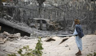 A man stands on the rubble of a house destroyed by a Saudi-led airstrike on the outskirts of Sanaa, Yemen, Tuesday, June 9, 2015. A series of airstrikes from the Saudi-led military coalition also targeted Yemen's Defense Ministry building, which is under control of Shiite rebels who control the capital, Sanaa, officials said. (AP Photo/Hani Mohammed)