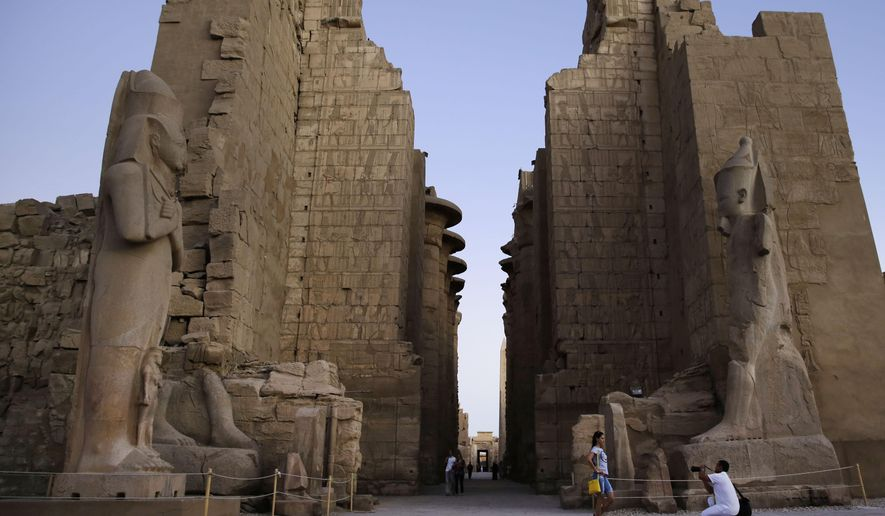A tourist has her picture taken at the ruins of the Karnak Temple in Luxor, Egypt, in this Sunday, Nov. 30, 2014, file photo. Egyptian officials say a suicide bomber has blown himself up at the ancient temple of Karnak in Luxor, a southern city frequented by millions of foreign and Egyptian tourists every year. (AP Photo/Hassan Ammar, File)
