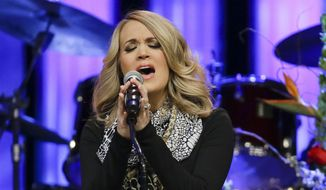 Carrie Underwood performs during the funeral service for Little Jimmy Dickens in the Grand Ole Opry House in Nashville, Tenn. on Jan. 2, 2015. Ms. Underwood is the top contender for the 2015 CMT Music Awards with five nominations. The CMT Awards will air live from the Bridgestone Arena in Nashville on Wednesday, June 10. (AP Photo/Mark Humphrey, File)